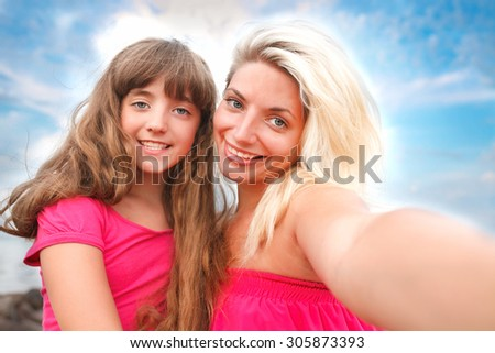 mother and  daughter are doing Selfe on the beach