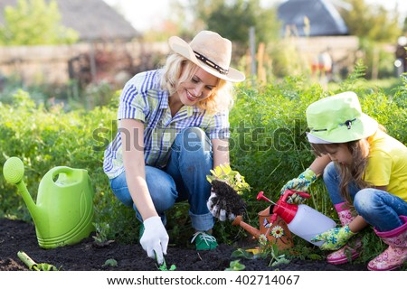 Mother and Daughter Child Watering Plants in Garden.