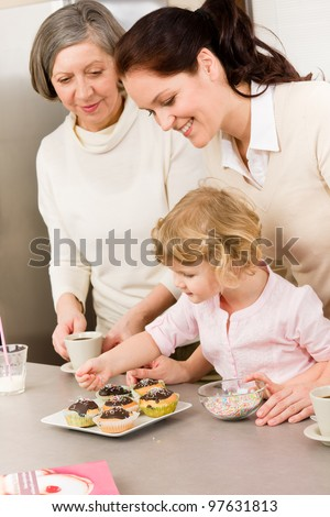 mother and daughter decorating cupcakes sprinkles happy together at home