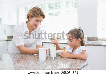 Mother and daughter having breakfast at home in kitchen