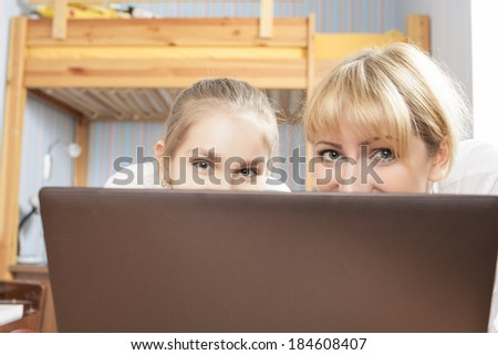 Mother and Daughter In Front of computer Screen Looking With Smile. Horizontal Image