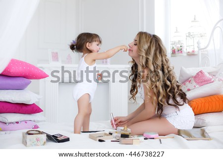 Mother and daughter in white having fun doing lip make-up. Mother and daughter doing makeup sitting on the bed in the bedroom