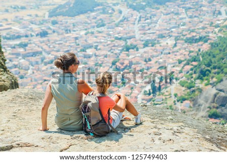 Mother and daughter looking at the town of Kalambaka bird's eye view. Meteora, Greece.