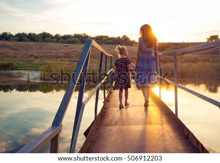 mother and daughter on a bridge through the rural river