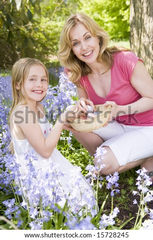 Mother and daughter on Easter looking for eggs outdoors smiling