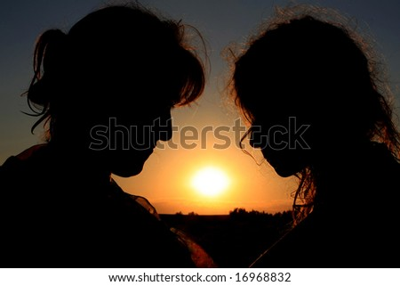 Mother and daughter silhouettes on sunset background