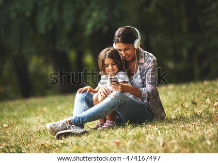 Mother and daughter sitting on grass and listening to music on smart phone.