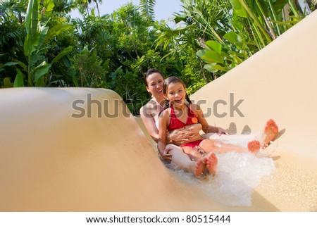Mother and Daughter Sliding Down Water Slide.