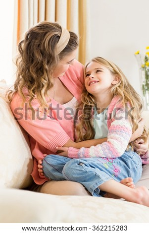 Mother and daughter smiling together on the couch