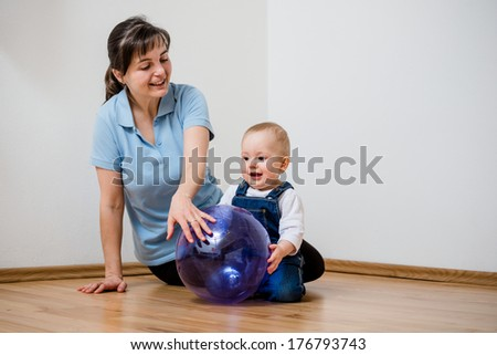 Mother and her baby play with inflatable ball at home on floor