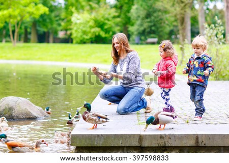 Mother and her children feeding ducks in summer park, adorable kid boy and girl, siblings having fun together