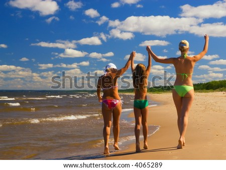 Mother and her two daughters walking on a beach