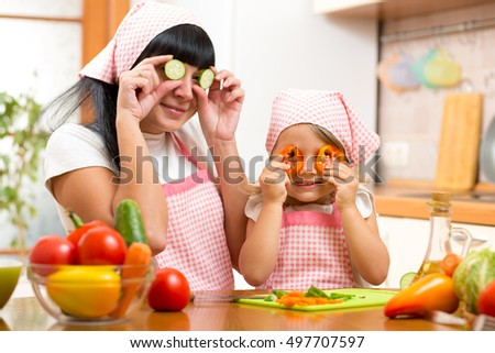 mother and kid daughter preparing healthy food and having fun