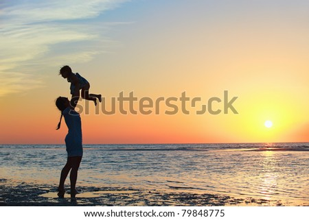 Mother and little daughter silhouettes on beach at sunset