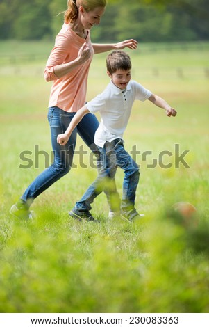 Mother and son playing football, outdoors