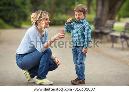 Mother and son playing outdoors creating soap bubbles