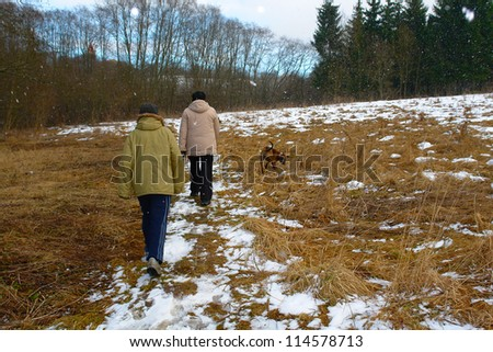Mother and son walking in a winter forest