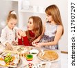 Mother and two daughter rolling dough in the kitchen. - stock photo
