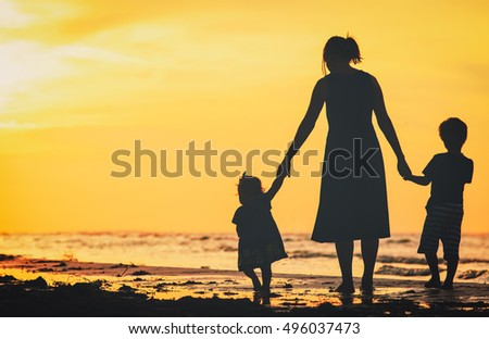mother and two kids walking on beach at sunset