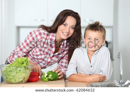 Mother cooking with son in kitchen