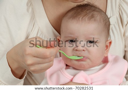 Mother feeds her little baby with spoon