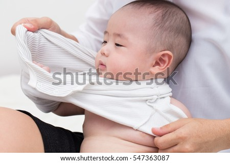 Mother getting dress for her baby