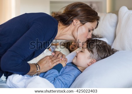 Mother giving good night kiss to sleeping son. Lovely mother putting son to bed. Happy young loving mother kisses son on forehead.