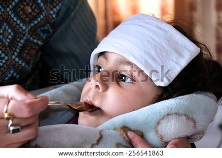 Mother giving syrup to her ill kid.