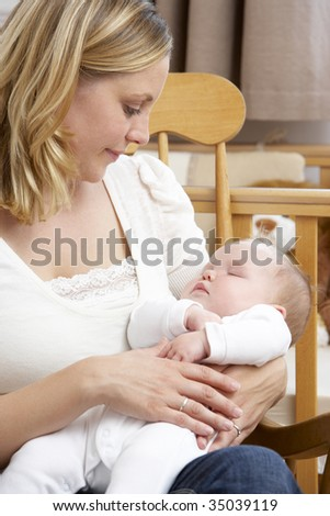 Mother Holding Baby In Nursery