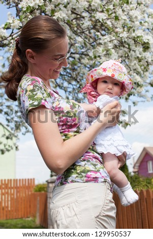 Mother holding her child in the garden with blossoming apple-tree