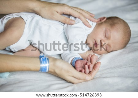 Mother holding her newborn son. Shallow dof, focus on hands with bracelets