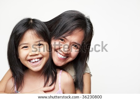 Mother hugging her daughter and posing to camera
