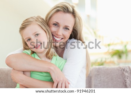 Mother hugging her daughter on the sofa
