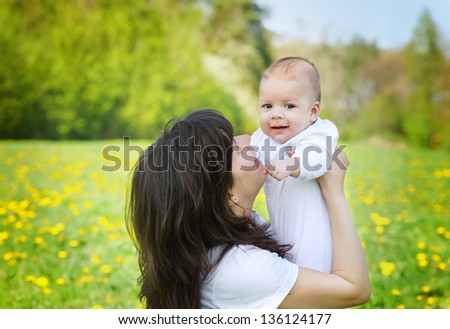 Mother hugging her little child boy in a park. Spring