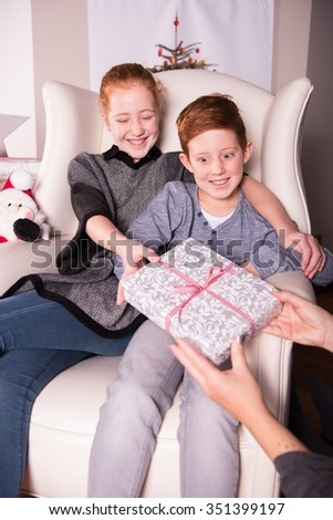 mother in the off is giving gift to her children