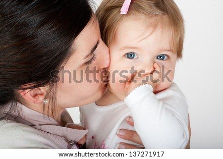 Mother kissing and playing with her cute baby girl