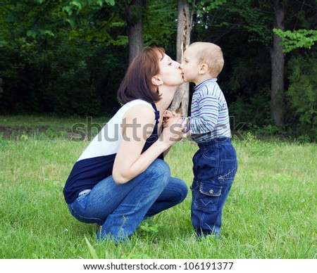 Mother kissing baby outdoors in the park