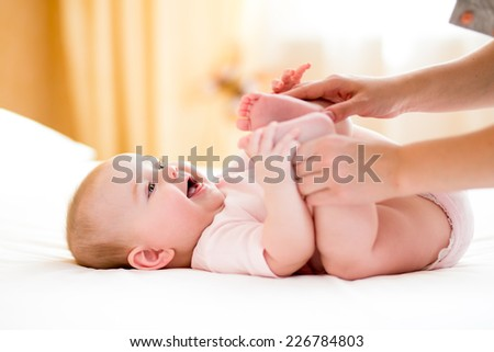 mother massaging or doing gymnastics to baby girl