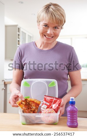 Mother Preparing Unhealthy Lunchbox In Kitchen
