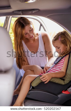 mother putting on security belt on daughter