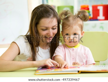 Mother reading book her child daughter at table