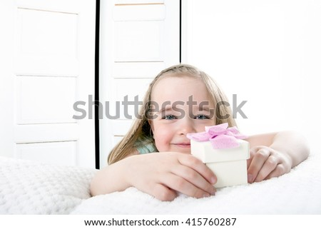 mother's day morning surprise wake-up: daughter handing over present beside the bed