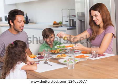 Mother serving vegetables to daughter at dinner in kitchen