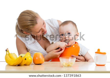 mother spoon feeding baby boy