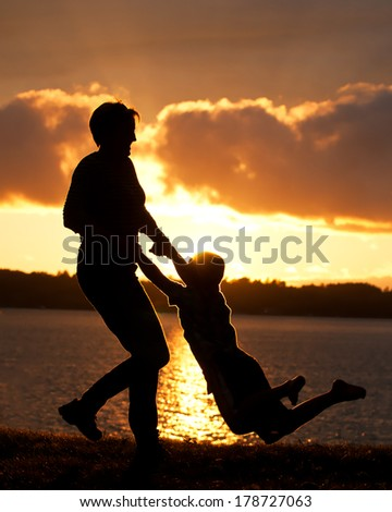 Mother Swings Young Son Silhouette Lake Background