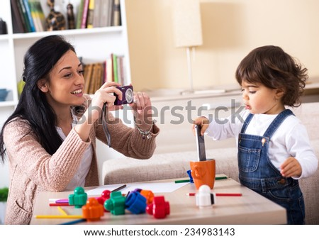 Mother taking a picture of her baby girl.They playing with toys in living room.
