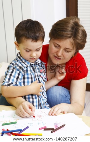 Mother teaches her son to draw
