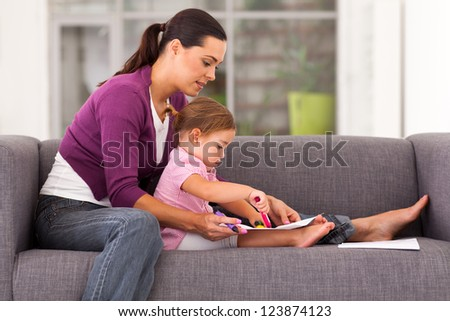 mother teaching daughter drawing on sofa at home