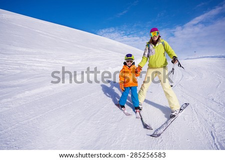 Mother teaching little boy 4 years old how to mountain ski going on the piste on resort