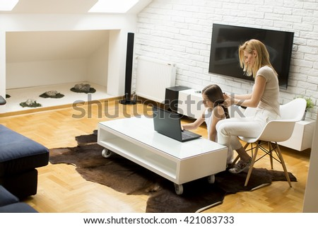Mother with a daughter on the laptop at home